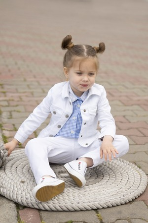 Stylish little baby is sitting on the ferry cable on the marina. She is dressed in fashionable designer clothes 写真素材