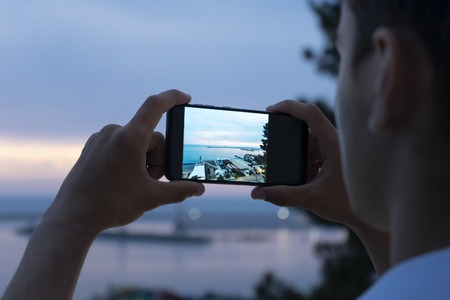 Mens hands holding smartphone and taking photo of beautiful sunset on the beach 写真素材