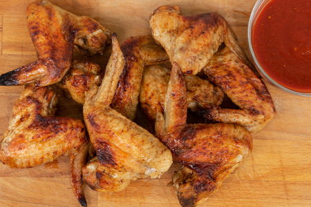 Chicken wings with red sauce on wooden background.
