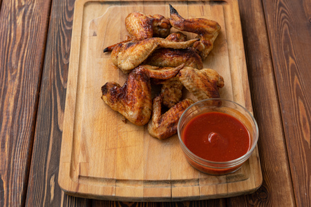 Deep fried chicken wings with red sauce on wooden background. Street food.