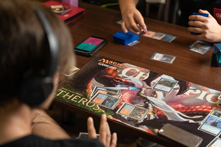 SOCHI, RUSSIA-MAY 17, 2019: Teenage with the headphones is playing the new part of the game The War of the Spark Magic The Gathering