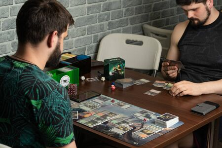 SOCHI, RUSSIA-MAY 17, 2019: Two bearded hipsters are playing a new part of the board game The War of the Spark Magic The Gathering lies