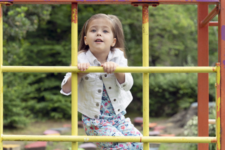 Little blonde girl of three to four years old are playing on the Playground, she is climbing on steel beams. Childrens outdoor development