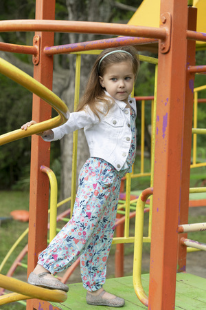 Little stylish blonde girl is having fun on a playground. Development of children in the open air in environmentally friendly conditions.