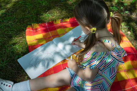 kid little girl is drawing with felt-tip pen in the park