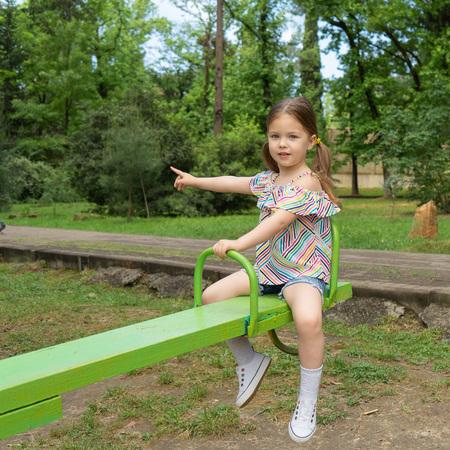 Kleine blonde meid van drie tot vier jaar oud rijdt op schommels op de speelplaats