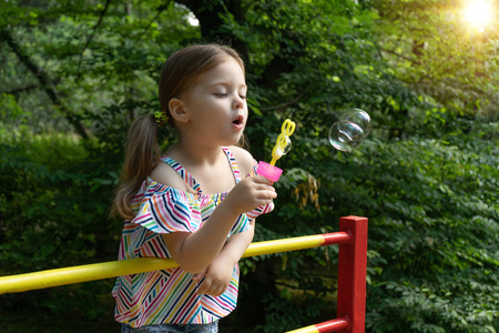 Pretty little girl is blowing a soap bubbles in summer day