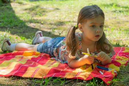 Little girl showing colorful felt-tip pens, Little girl three to four years old lies on a bright blanket in the garden, she holds in her hand colorful marker pens Stockfoto