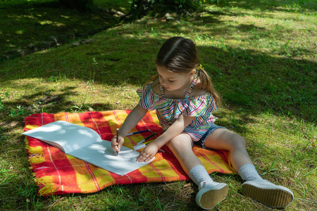 A little girl draws marker pens in an album in the Park, she sits on a colored blanket