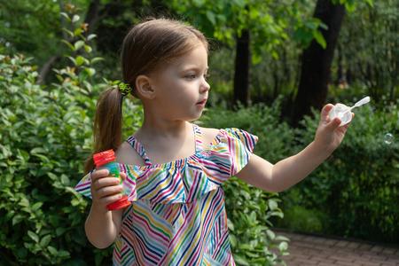 Cute little European girl blowing soap bubbles in the Park 写真素材