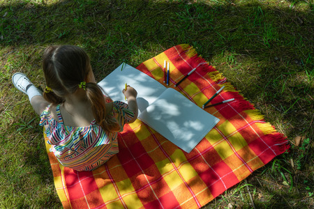 Little toddler is drawing outdoor using colorful felt tip pens. 写真素材