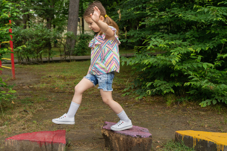 Little girl is playing on the Playground, In harmony with nature eco-Playground for children