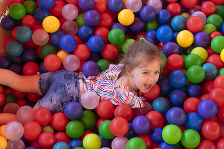 Baby girl is playing in playground with colourful balls 写真素材