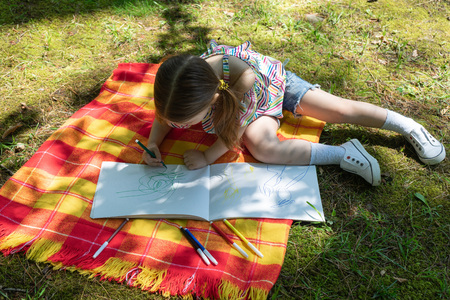 Kid draws in the album with colored pen markers.