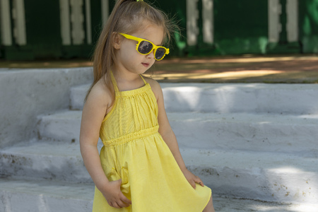 Kid dressed a yellow dress and sunglasses