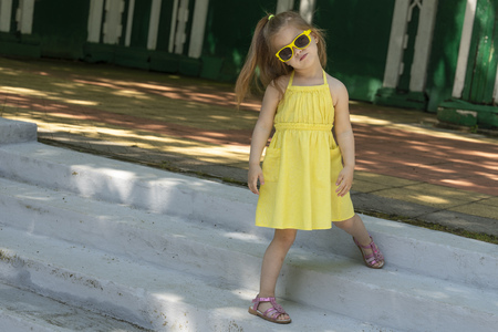 Kid modelis wearing a yellow dress. Child girl advertises fashionable childrens things participating in a photo shoot. 写真素材