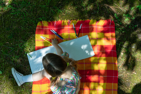 Little girl is painting with felt tip pens on the open air, Top view 写真素材