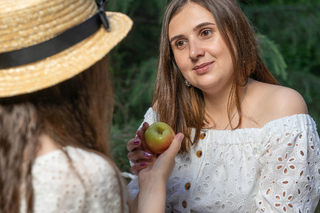 Mom and daughter on picnic, daughter is giving the apple to mother. Beauty nature scene with family outdoor.