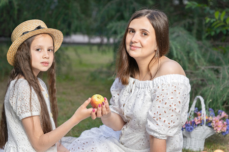 Mother and daughter on the picnic in the garden. Family resting together on the green grass among the coniferous trees. Healthy food. Family picnic.
