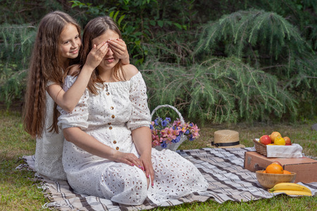 Mom and kid are playing outdoor. Girl closes eyes to her mom. Mother and daughter are sitting on checkered beige tablecloth for picnic next to straw basket with flowers and fruits 写真素材
