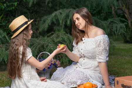Vegetarian family on a picnic. Mother and daughter dressed in white dresses they sit on the plaid and eat fruits. Healthy lifestyle and nutrition
