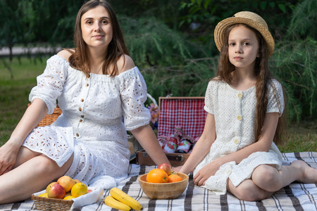 Portrait of family of two people. Brunette mom and daughter are enjoying a picnic in the park. Vegetarian family. Fresh fruits. Healthy lifestyle in the family