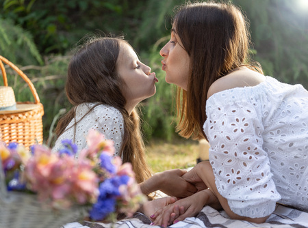 Mother and daughter are kissing each other laying on blanket at a picnic in a park.