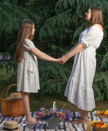 Mother and daughter dressed in white dresses, with long hair are holding each others hands. Mother and daughter picnic 写真素材