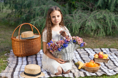 Portrait of a pretty girl with a basket of flowers on a picnic in the park. Space for a picnic with fruits, flowers, and a wicker basket