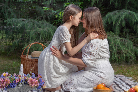 Happy mom and daughter are holding each other gently on the grass during a picnic in a park, There are a basket with flowers and fruits