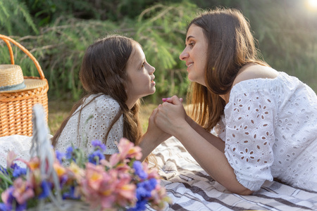 orgeous mother and daughter in white dress. Picnic in good summer day at sunset. Outdoor portrait of pretty girl is spending time with mother in the garden.