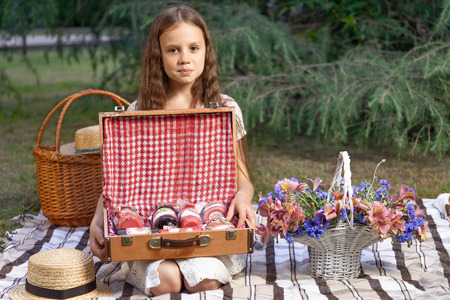 Portrait of a beautiful girl with a basket of flowers on a picnic in the park. The child holds open a chest with jam