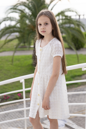 Portrait of little fashion girl on the background of the palm. Young photo model with full lips