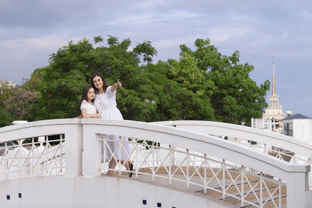 Family on vacation at the hotel. Mom shows her daughter the sights. Girls dressed in white dresses are on the bridge. 写真素材