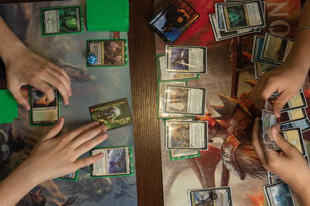 SOCHI, RUSSIA-MAY 17, 2019: Two teenagers are playing in board game Magic The Gathering War of the Spark. Top view 報道画像