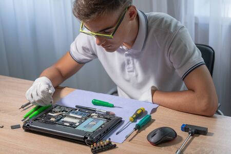 .Young male engineer repairs a laptop. Electronics repair service concept.