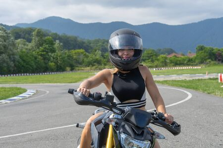 Young woman on the sport motorcycle in a bike helmet on the motor track