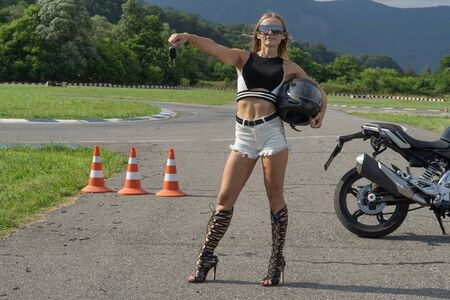 Sexy blonde in short shorts on the motor track is trained in a driving school. Slender girl shows motorcycle keys