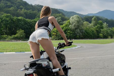 Sexy blonde in jeans shorts of young pretty girl sitting on motorcycle. Slender female legs by motorbike, view from the back