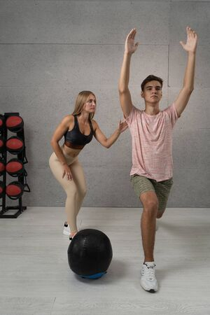 Young man working out with personal trainer at the gym. Exercises with ball