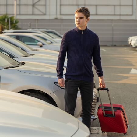 A young man with a red luggage bag, chooses a car to rent. Auto business concept.