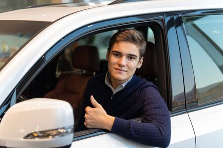 Happy customer, buying a new car. He's gesturing thumbs up sitting inside a car. Reklamní fotografie