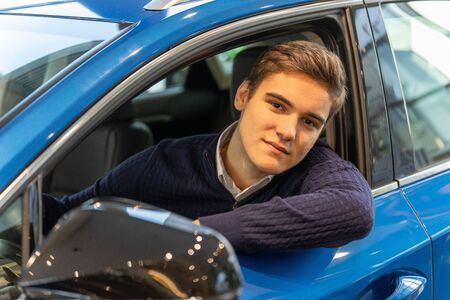 Portrait of a young customer sitting in a new car. Buying a vehicle at a dealership Reklamní fotografie