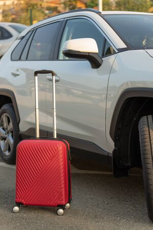 Red luggage bag next to the car. The concept of airport transfer or taxi