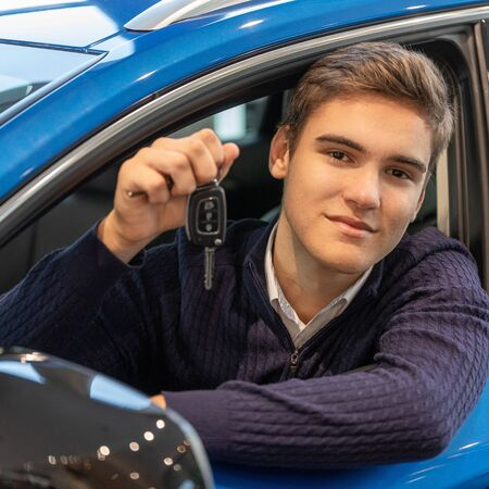 Happy young customer sitting in new car and shows the key