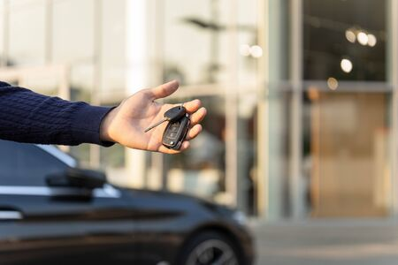 Hand with keys from a luxury black car on the background of the dealership. Dealership of rent, hire cars. Carsharing