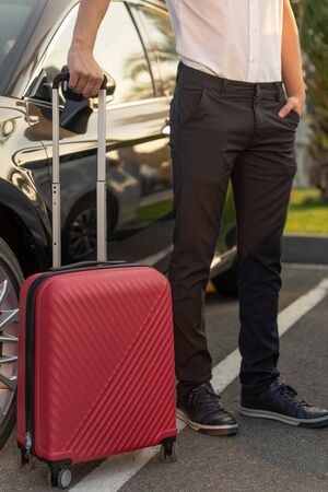 Man with a red luggage bag next to the black car. The concept of airport transfer or taxi Reklamní fotografie