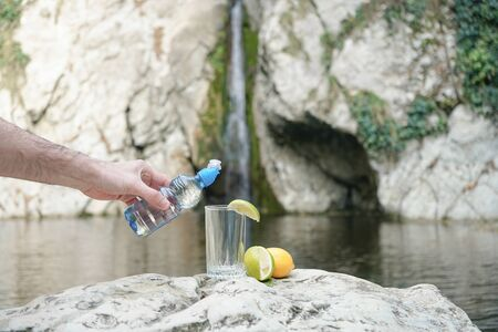 Pouring mineral natural drinking water from a biodegradable plastic bottle with sport-lock lid into a glass, which male hand holding in front of a mountain stream in the Alps