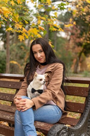 Caucasian girl with a dog sitting on a bench in the park.