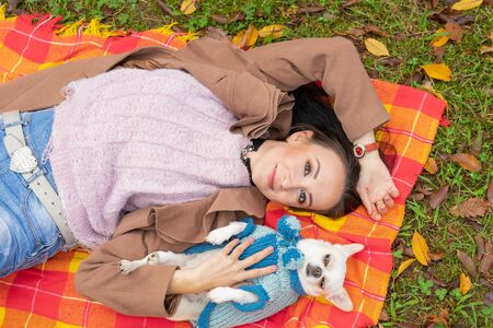 Girl lying on the lawn with a pet dog. Reklamní fotografie